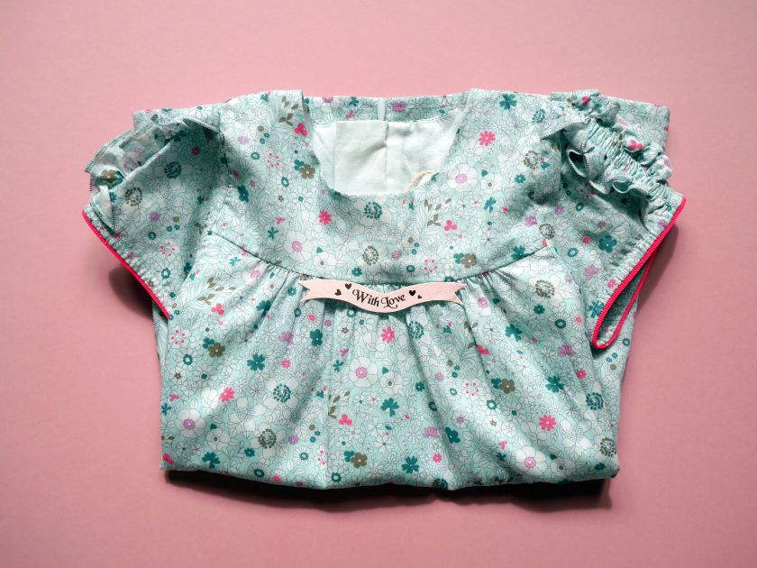 folded baby dress with a note pink